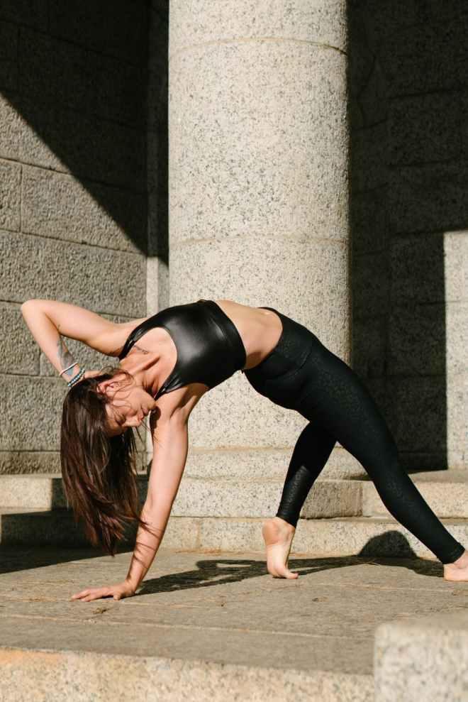 woman in black tank top and black leggings bending her body